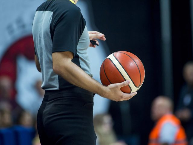 Basketball referee holding a basketball at a game in a crowded sports arena